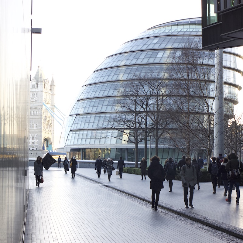 People walking in More place, with London City Hall in the background.